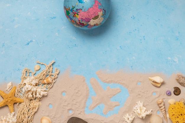 Draufsicht von muscheln, weltkugel und seesternen auf einem strand