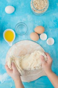 Draufsicht von nahrungsmitteln als butterei-haferflocken mit frauenhandkneteteig auf blauem hintergrund