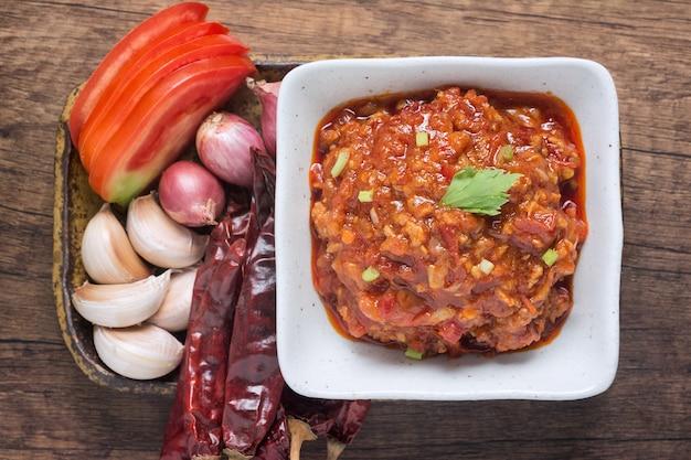 Draufsicht von (nam prik ong) nordthailändisches fleisch und tomate-würziger dip in einer weißen schale.