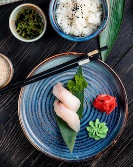 Draufsicht von nigiri-sushi auf bambusblatt serviert mit ingwer und wasabi auf einem teller