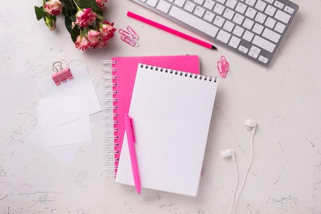 Draufsicht von notizblöcken auf schreibtisch mit blumenstrauß von rosen
