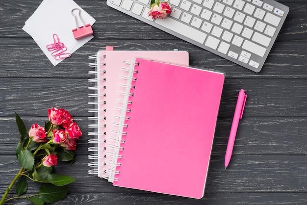 Draufsicht von notizbüchern auf hölzernem schreibtisch mit blumenstrauß von rosen und von klebrigen anmerkungen