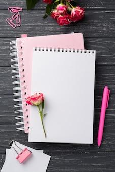 Draufsicht von notizbüchern auf hölzernem schreibtisch mit blumenstrauß von rosen und von stift