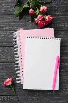 Draufsicht von notizbüchern auf hölzernem schreibtisch mit blumenstrauß von rosen