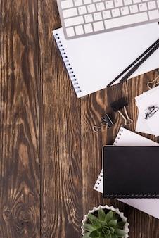 Draufsicht von notizbüchern auf hölzernem schreibtisch mit kopienraum