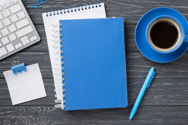 Draufsicht von notizbüchern auf hölzernem schreibtisch und kaffeetasse