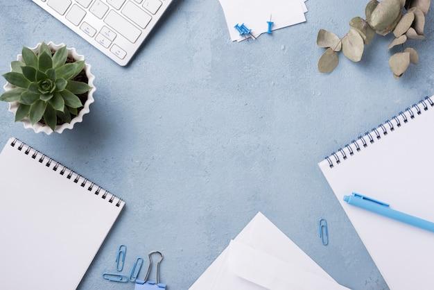Draufsicht von notizbüchern auf schreibtisch mit saftiger anlage und büroklammern