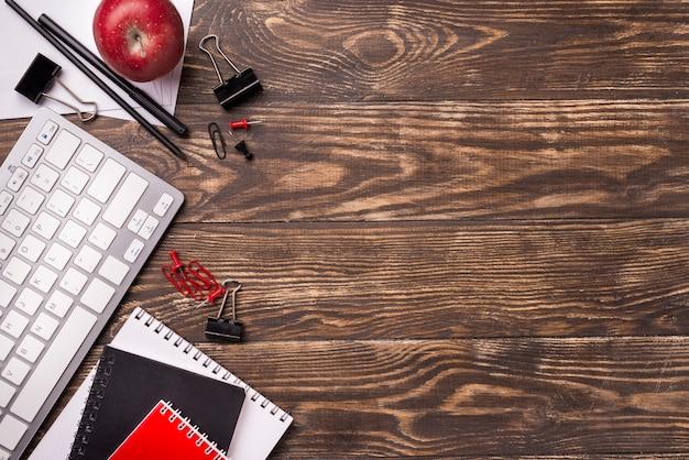 Draufsicht von notizbüchern und von apfel auf hölzernem schreibtisch mit kopienraum