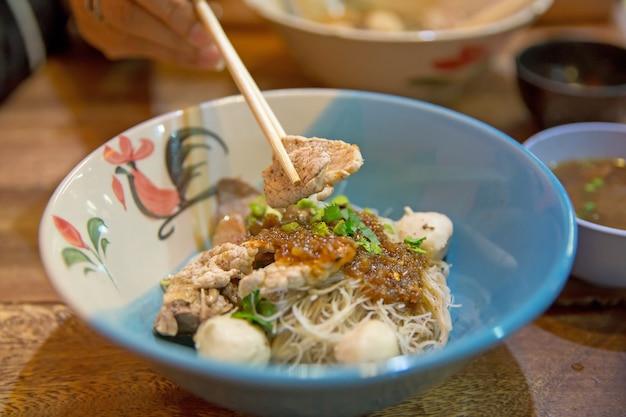 Draufsicht von nudeln mit schweinefleisch und schweinefleischbällchen mit suppe thailändischer art. thailändische völker nennen bootsnudeln