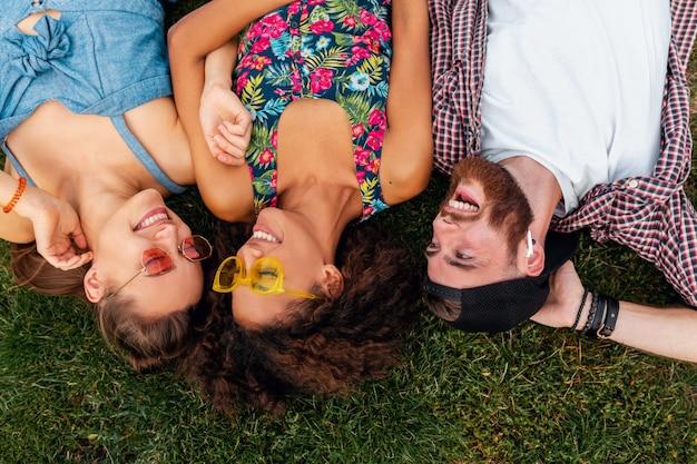 Draufsicht von oben auf bunte stilvolle glückliche junge gesellschaft von freunden, die auf gras im park liegen, mann und frauen, die spaß zusammen haben
