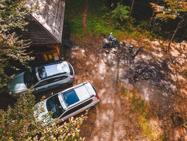 Draufsicht von oben auf den grillplatz im wald zwei geparkte geländewagen