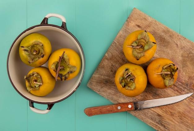 Draufsicht von orange persimmonfrüchten auf einem hölzernen küchenbrett mit messer mit persimmonfrüchten auf einer schüssel auf einem blauen holztisch