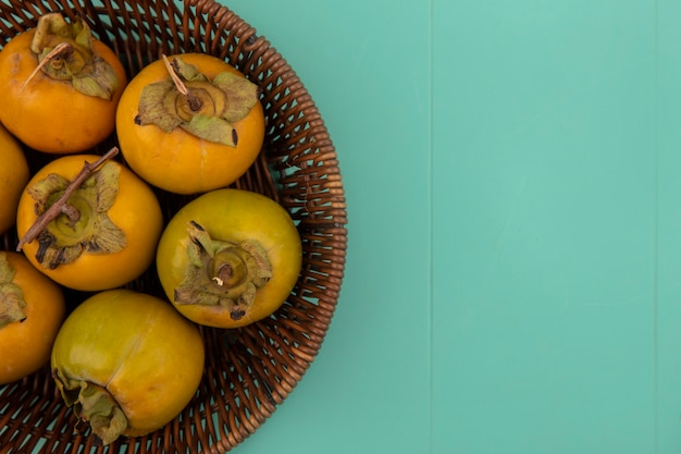Draufsicht von orange unreifen kakifrüchten auf einem eimer auf einem blauen holztisch mit kopienraum