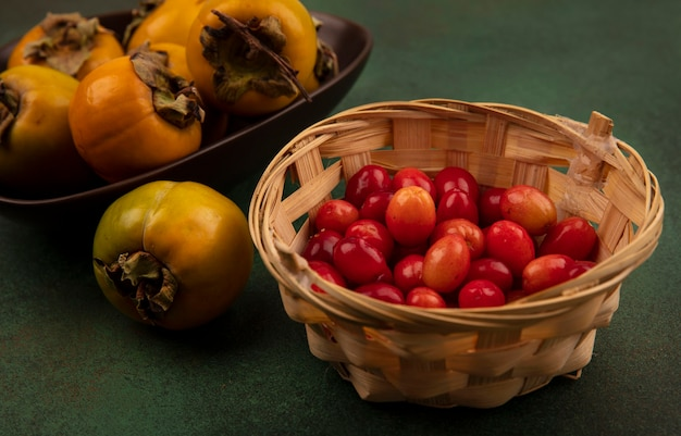 Draufsicht von orangefarbenen persimonenfrüchten auf einer schüssel mit kornelkirschen auf einem eimer auf einer grünen oberfläche