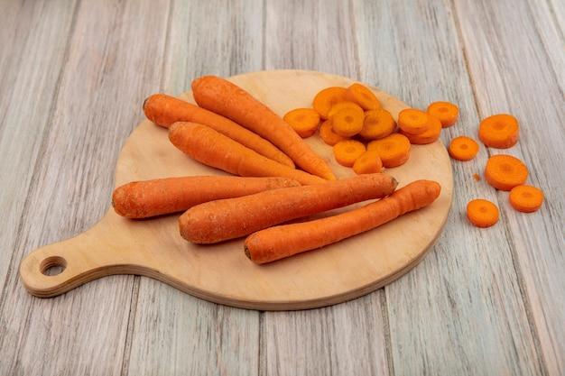 Draufsicht von orangenwurzelgemüse-karotten auf einem hölzernen küchenbrett mit gehackten karotten auf einer grauen holzoberfläche