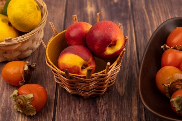 Draufsicht von organischen pfirsichen auf einem eimer mit mandarinen mit kakis lokalisiert auf einer holzwand