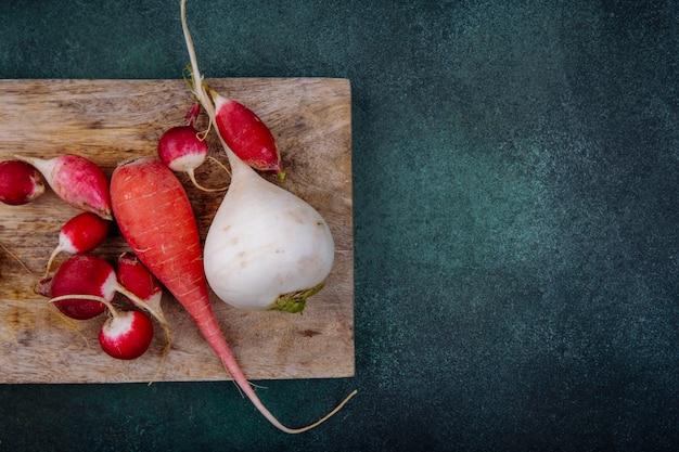 Draufsicht von organischen weißen und rosaroten wurzelgemüse-rote beete auf einem hölzernen küchenbrett mit radieschen auf einer grünen oberfläche mit kopierraum