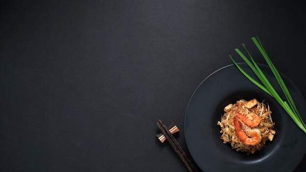 Draufsicht von pad thai, fliege der thailändischen nudel mit garnelen und ei in schwarzer keramikplatte auf schwarzem tisch rühren