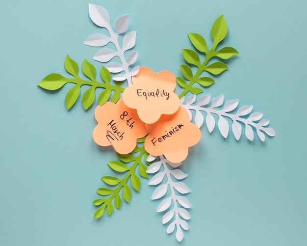 Draufsicht von papierblumen mit blättern für frauentag
