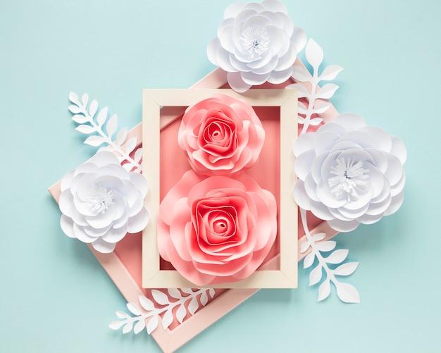 Draufsicht von papierblumen mit holzrahmen für frauentag