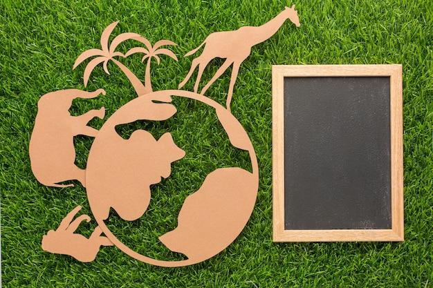 Draufsicht von papiertieren und planeten mit tafel auf gras für tiertag