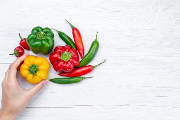 Draufsicht von paprika mit würzigen paprikaschoten auf leichtem, pflanzlichem scharfem speisenmehl roh
