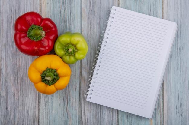 Draufsicht von paprika und notizblock auf hölzernem hintergrund mit kopienraum