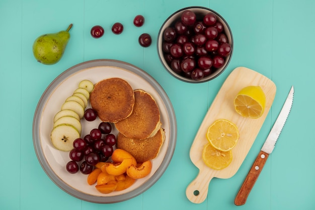 Draufsicht von pfannkuchen mit geschnittener aprikose und birne und kirschen in platte mit geschnittener zitrone auf schneidebrett und schüssel kirschen mit messer auf blauem hintergrund