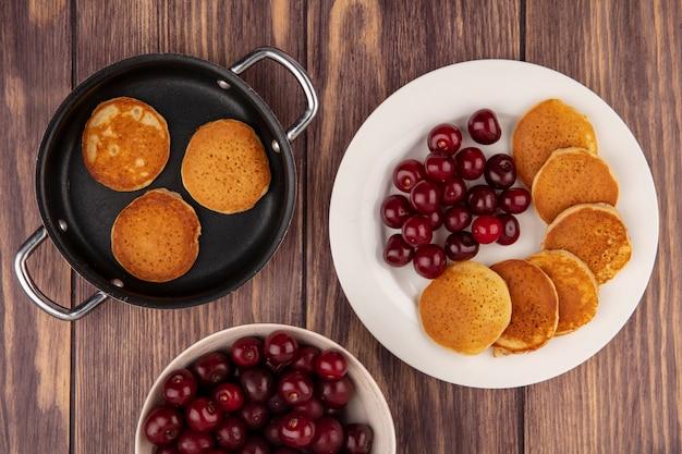 Draufsicht von pfannkuchen mit kirschen in platte und pfannkuchenpfanne mit schüssel kirschen auf hölzernem hintergrund
