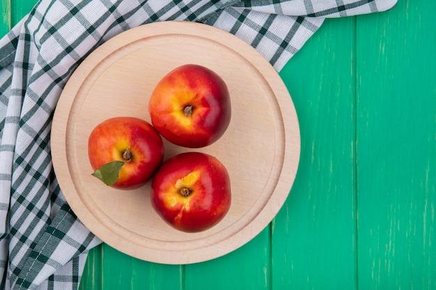 Draufsicht von pfirsichen auf einem holztablett mit einem karierten handtuch auf einer grünen oberfläche
