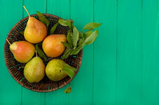 Draufsicht von pfirsichen im korb auf grüner oberfläche