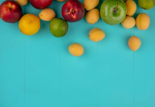 Draufsicht von pfirsichen mit äpfeln aprikosen zitrone und limette auf einer blauen oberfläche