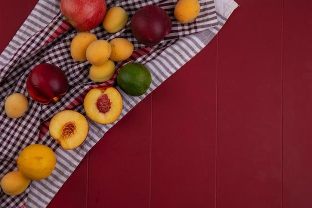 Draufsicht von pfirsichen mit apfel und aprikose auf einer roten oberfläche