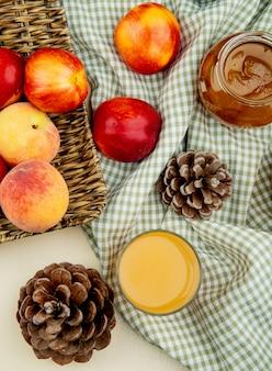 Draufsicht von pfirsichen pfirsichsaft und marmelade mit tannenzapfen auf kariertem stoff auf weiß