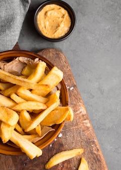 Draufsicht von pommes frites in der schüssel mit salz und senf