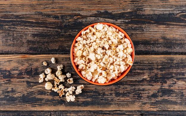 Draufsicht von popcorn in der schüssel auf dunklem holz horizontal
