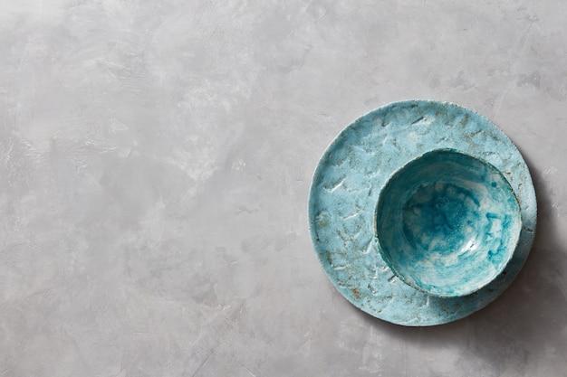 Draufsicht von porzellangeschirr handgemacht auf einem grauen marmortisch mit raum unter text. traditionelle dekorative keramik handgefertigt.