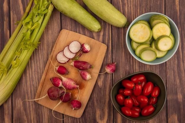 Draufsicht von radieschen auf einem hölzernen küchenbrett mit gehackten zucchini auf einer schüssel mit tomaten auf einer schüssel mit sellerie und zucchini lokalisiert auf einer holzwand