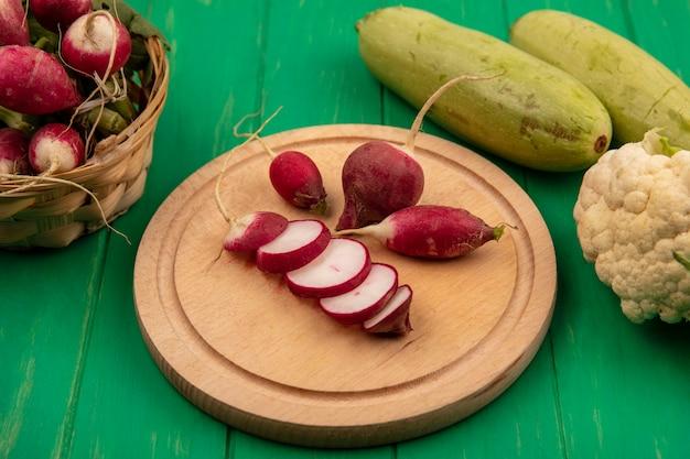 Draufsicht von radieschenscheiben lokalisiert auf einem hölzernen küchenbrett mit ganzen radieschen auf einem eimer mit zucchini und blumenkohl isoliert auf einer grünen holzwand