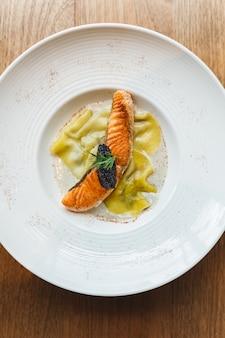 Draufsicht von ravioli in sahnesauce mit gegrilltem lachs mit kaviar.