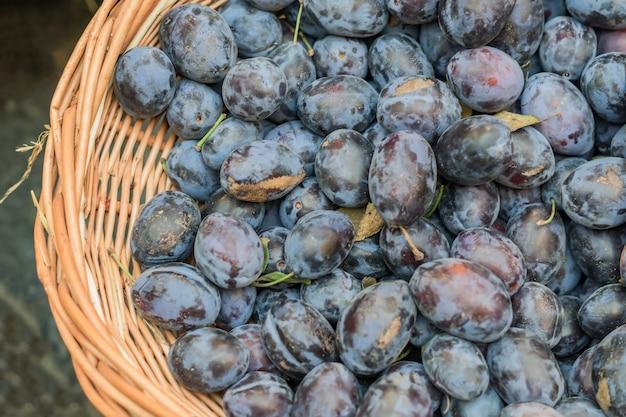 Draufsicht von reifen pflaumen in einem korb am markt des landwirts