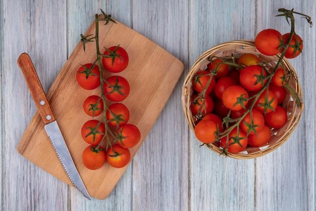 Draufsicht von reifen weinreben-tomaten auf einem hölzernen küchenbrett mit messer mit weinreben-tomaten auf einem eimer auf einem grauen hölzernen hintergrund