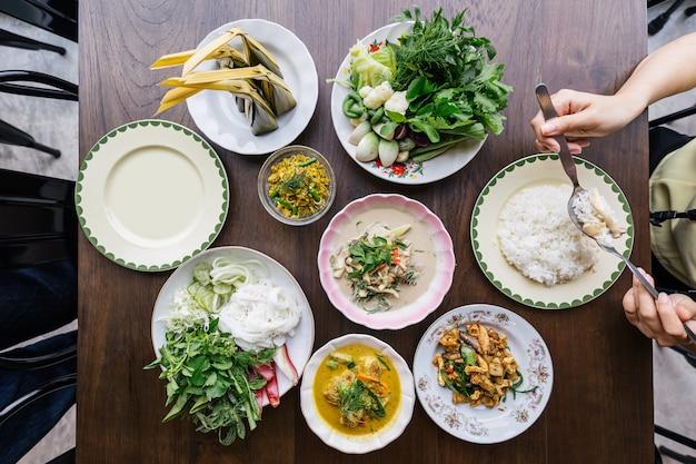 Draufsicht von reisnudeln mit krebsfleisch-currysoße, gedient mit gemüse. aufruhr fried spicy minced pork mit kräutern. würzige knusprige schweinehaut und pilzsuppe. klassische thailändische küche mit dampfreis.