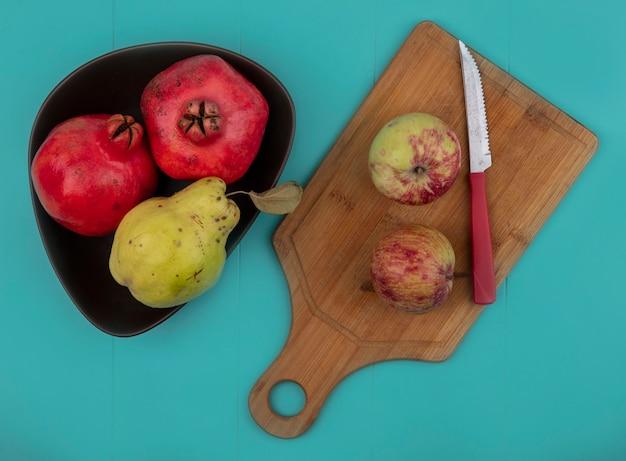 Draufsicht von rötlichen frischen granatäpfeln auf einer schüssel mit äpfeln auf einem hölzernen küchenbrett mit messer auf einem blauen hintergrund