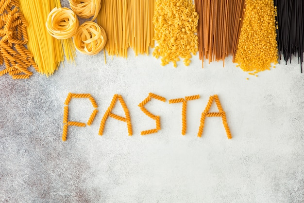 Draufsicht von rohen italienischen teigwaren mit kopienraum auf weißem cocnrete hintergrund. flache lage des italienischen essens