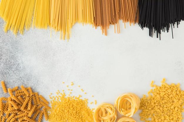 Draufsicht von rohen italienischen teigwaren mit kopienraum auf weißem steinhintergrund. flache lage des italienischen essens