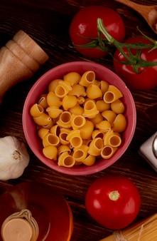 Draufsicht von rohrnudeln in der schüssel mit salz-tomatenbutter auf holzoberfläche