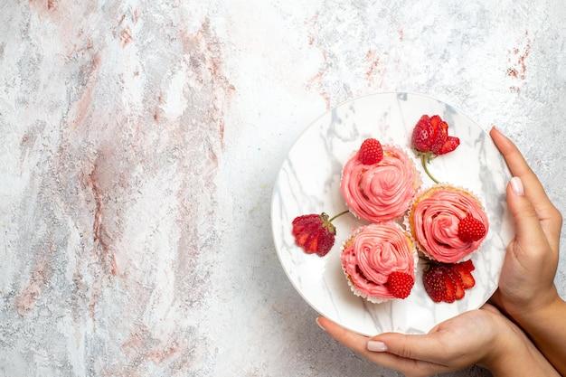Draufsicht von rosa erdbeerkuchen mit frischen roten erdbeeren auf weißer oberfläche