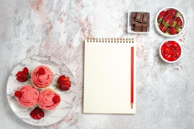 Draufsicht von rosa erdbeerkuchen mit marmelade und schokoriegeln auf weißer oberfläche
