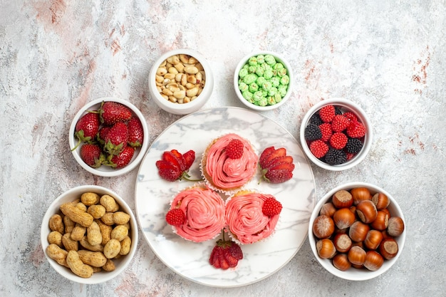 Draufsicht von rosa erdbeerkuchen mit nüssen und bonbons auf weißer oberfläche